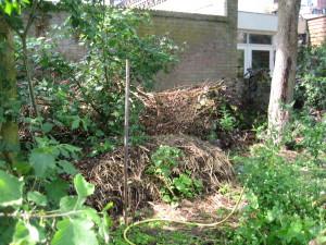 Composthoop, met op de achtergrond een houtril